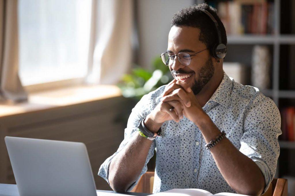 Happy man browsing on laptop.